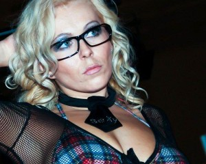 Curly Ann mit Brille, der Look macht an und das weiß sie auch. Das Foto ist von ihrer Website www.curlyann.com